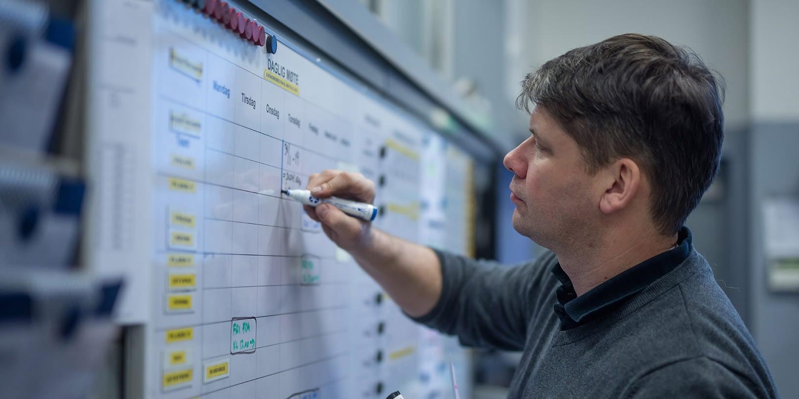 Ansatt på verksted hos Bilservice bilSpiten som noterer på en tavle montert på verkstedet med oversikt over dagen gjøremål